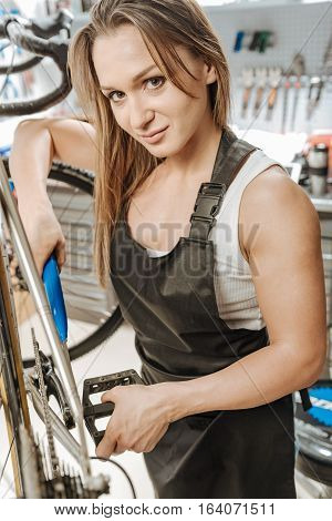 Woman enjoying male responsibilities. Charismatic athletic young woman standing in the workshop near the bicycle and working while fixing the pedal and expressing joy