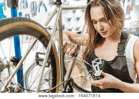 Involved in the process. Strong mindful muscular craftswoman standing in the garage near the bicycle and working while fixing the pedal and holding the screwdriver