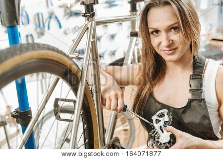 Delighted from my responsibilities. Athletic delighted muscular craftswoman standing in the workshop near the bicycle and working while fixing the pedal