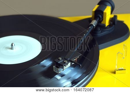 Vinyl LP record with white label sound reproduction on vintage turntable record player with yellow case. Horizontal photo closeup
