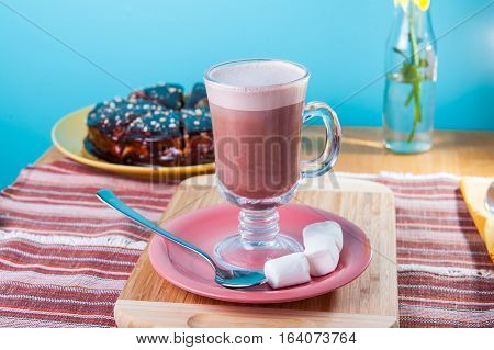 Glass Of Hot Cocoa With Marshmallows On The Table. Selective Focus, Blue Background.