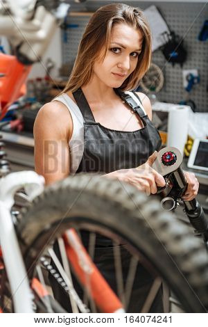 Doing my job properly. Charming athletic young mechanic standing in the garage and working while repairing the bicycle and holding the nut wrench