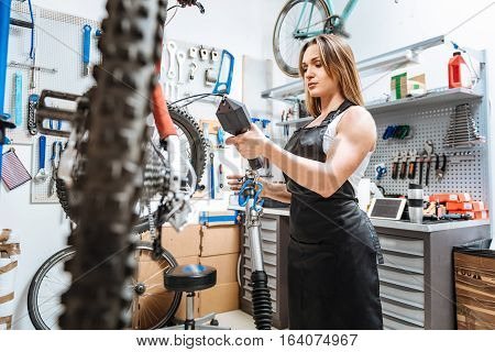 Checking weight of all details. Involved attentive serious craftswoman standing in the workshop and working while repairing the mountain bicycle and weighting all details one by one.