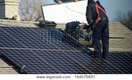 Solar energy panels being installed on a residential home roof. All labels of any copyright equipment have been removed.