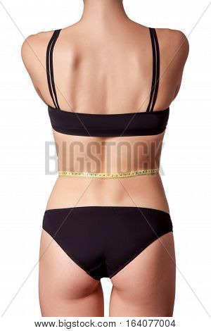 Slim fit happy young woman with measure tape measuring her waist with black underwear, isolated on white background. studio shot.