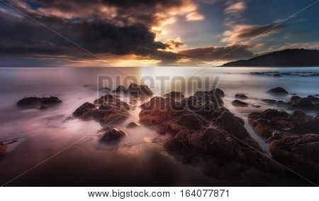 Dramatic sunset and a low tide on the beautiful coastline of Rotherslade Bay, a small bay in South Gower next to the more famous Langland Bay.