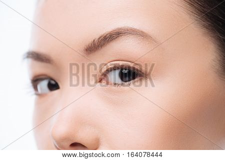 Fixed gaze. Nice beautiful Chinese woman standing against white background and looking at you