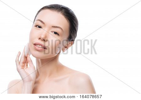 Facial cleansing. Joyful cute young woman holding a cotton pad and smiling while cleaning her skin