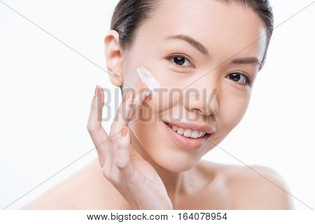 Always stay young. Positive charming attractive woman putting facial cream on her cheek and smiling while caring about her face poster