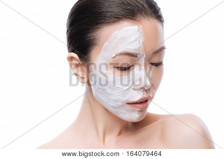 Skin cosmetics. Charming pleasant asian woman using moisturizing cream and looking down while making a facial mask