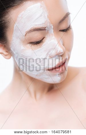 Daily skin care. Cute attractive young woman closing her eyes and having cream on the half of her face while doing her daily skin care activities