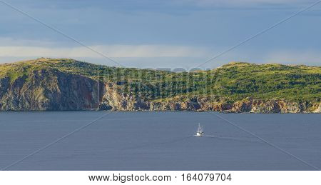 Late afternoon sun shines on an outcropping of high rugged terrain in calm sea water as a sailboat under motor power, goes along in the bay at Twillingate, Newfoundland, Canada.