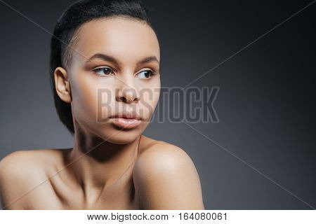Healthy skin. Beautiful attractive young woman standing against the black background and turning her head while pulling her shoulders forward
