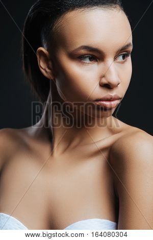 Perfect skin. Beautiful attractive young woman turning her head and looking aside while posing against the black background