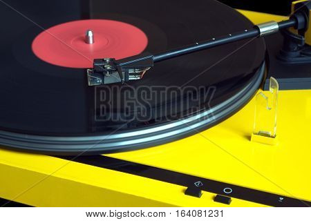 Turntable in yellow case playing a vinyl record with red label. Horizontal photo isolated on black background closeup