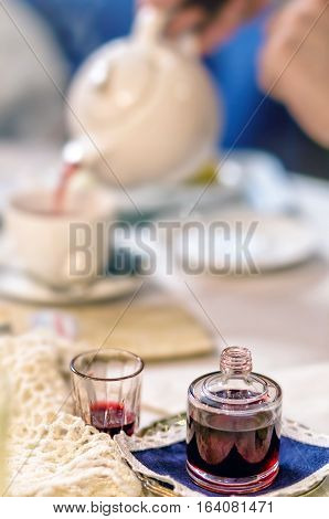 Cherry liqueur pouring into a glass and tea