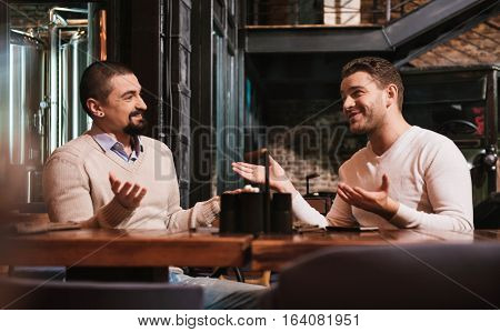 Being emotional. Delighted handsome nice men looking at each other and gesticulating while having a conversation