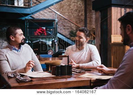 Pleasant conversation. Delighted nice good looking men sitting together and discussing something while meeting in the pub