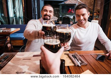 Positive pleasant nice man holding glasses and looking at you while drinking beer