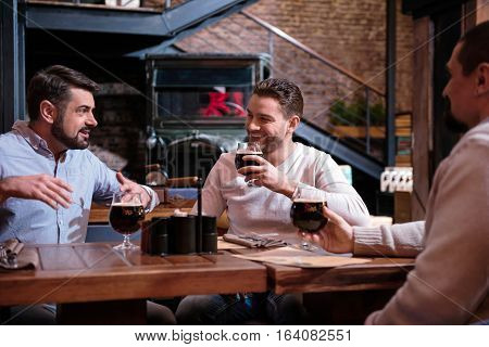 Pleasant meetings. Cheerful happy handsome men meeting in the pub and drinking beer while having an interesting conversation