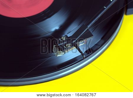 Working vinyl LP record with red label sound reproduction on vintage turntable record player with yellow case. Horizontal photo top view closeup