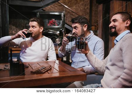 Resting together. Delighted nice pleasant men holding glasses with beer and watching football while resting together in the pub