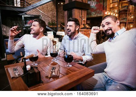 Interesting football match. Positive handsome nice men sitting at the table and showing their emotions while watching football in the pub