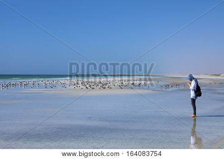 MIRBAT, OMAN - JANUARY 07,2016: A young girl is standing by the Indian Ocean coast near Mirbat, Oman.