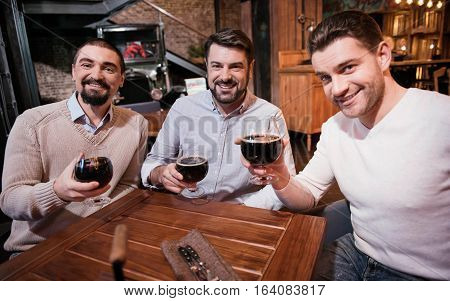 Good company. Handsome nice cheerful men raising glasses with beer and smiling while enjoying time in a good company