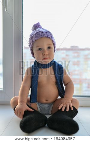 Businesslike little baby boy comfortable sitting near the window weared in winter clothes.
