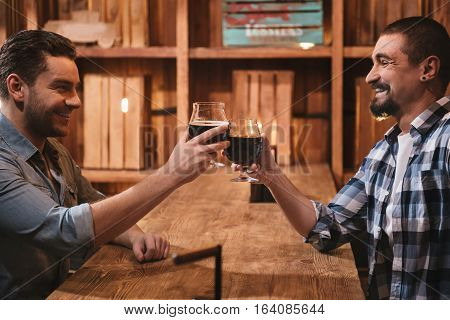Nice company. Positive cheerful male friends sitting opposite each other and cheering with beer while going out together