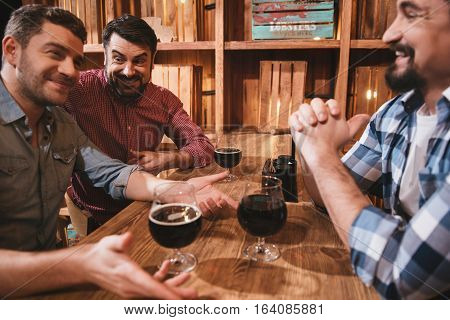 Meeting of best friends. Delighted positive handsome friend having glasses with beer in front of them and chatting while enjoying their time together