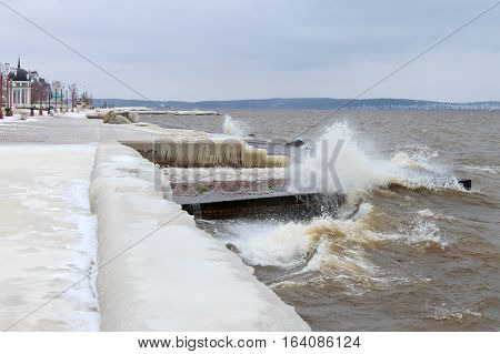 Winter storm on the lake and city embankment covered with ice. Lake Onega, Petrozavodsk, Russia