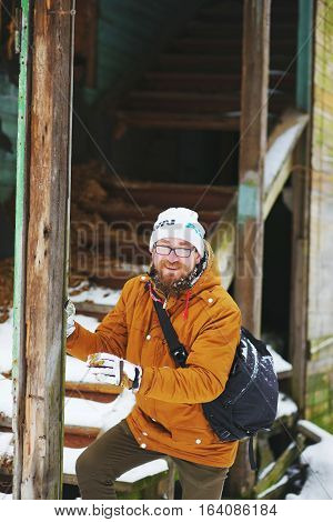 A young handsome bearded man with glasses standing near an old two-story wooden house and laughs in the winter.