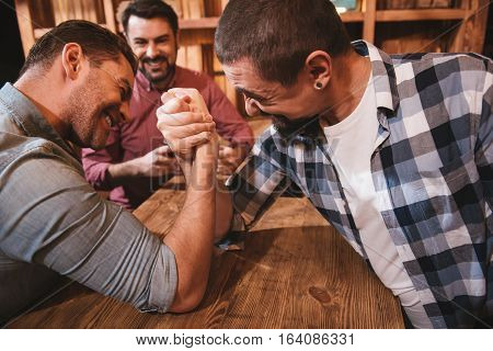 Having fun. Handsome strong pleasant man sitting opposite each other and having an armwrestling match while having fun in the pub