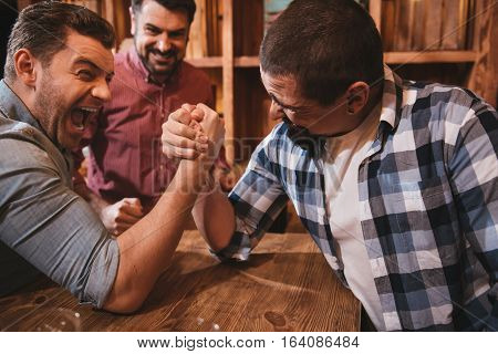 Brutal strength. Strong brutal handsome men sitting opposite each other and armwrestling while entertaining themselves in the pub