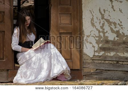 Girl in medieval dress reading book  on the doorstep of old house.