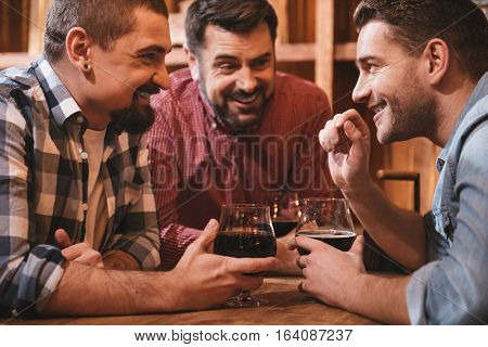 Communication with friends. Joyful smiling delighted man looking at his friends and telling them an interesting story while meeting in the pub