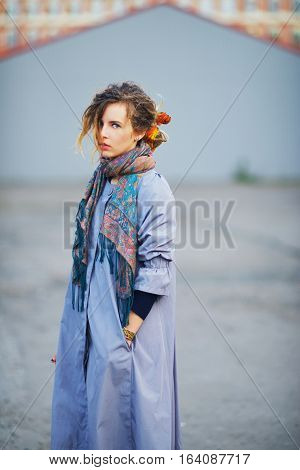 Young charming girl in a lavender cloak with a tippet about the neck on a walk through the city