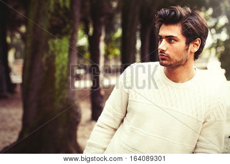 Handsome serene and pensive young man model in a trees park. Charming young and handsome man with stylish hair and white sweater. Outdoors in a park with a series of trees. Peaceful and calm attitude.