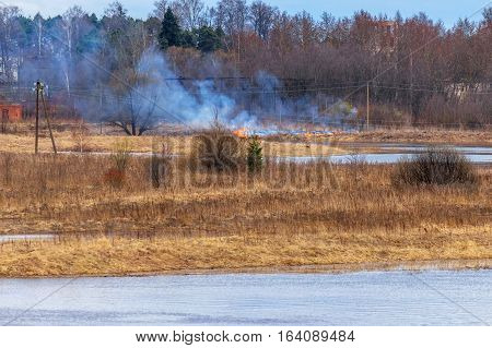 Burning dry grass in dangerous proximity to the village.