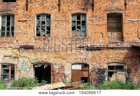 facade of the old red brick building with broken windows and traces of vandalism. can be used as demolition, earthquake, bomb, terrorist attack or natural disaster concept.