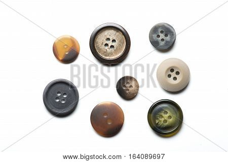 Collection of eight sewing buttons on white background