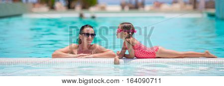 Mother and kid enjoying summer vacation in swimming pool
