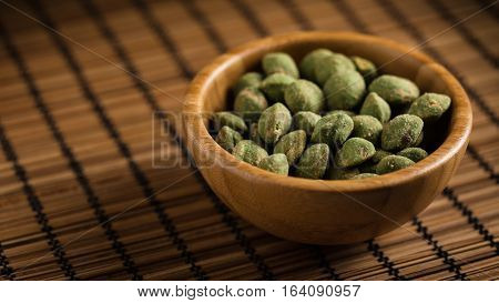 wooden bowl filled with wasabi covered peanuts