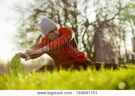 Young sportsman working-out in a park, stretching hamstrings before running