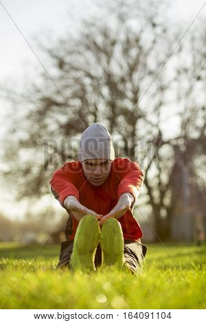 Young sportsman working-out in a park, stretching hamstrings before running.