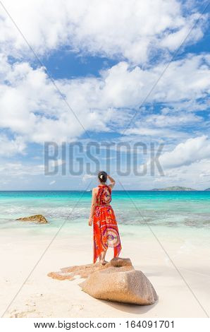 Traditinaly dressed local woman wearing long floral summer dress relaxing, doing yoga on Anse Patates beach, La Digue Island, Seychelles. Summer vacations on picture perfect tropical island concept.