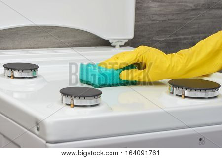 Hand In Yellow Glove Cleaning White Stove With Green Sponge