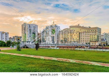 BELGOROD RUSSIA - JULY 04 2016: Pedestrian bridge over river Vezelka on the campus of Belgorod State University. View of the university hostel and left-bank residential neighborhood.
